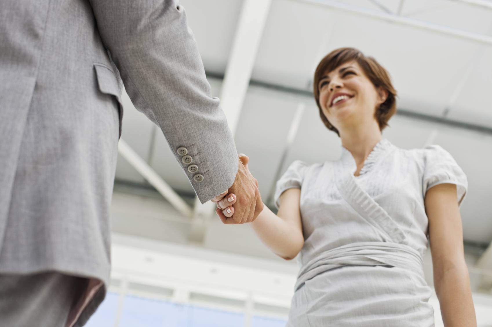 Closeup of happy young business colleagues shaking hands in the office
